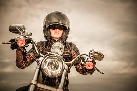 biker girl: Biker girl in a leather jacket and helmet on a motorcycle