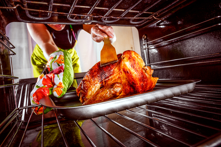 christmas cooking: Housewife prepares roast chicken in the oven, view from the inside of the oven. Cooking in the oven. Stock Photo