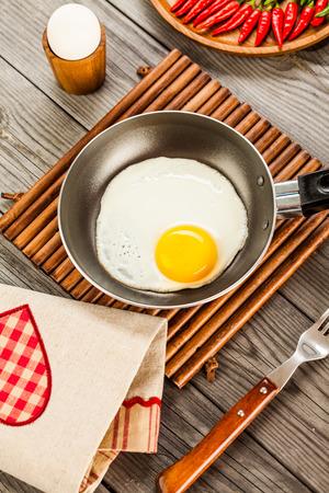 huevos estrellados: Huevos fritos sobre una mesa de madera, desayuno Foto de archivo