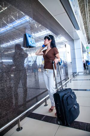 lateness: Woman calling on the phone at the airport