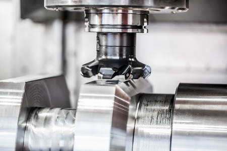 production area: Metalworking CNC milling machine. Cutting metal modern processing technology. Small depth of field. Warning - authentic shooting in challenging conditions. A little bit grain and maybe blurred.