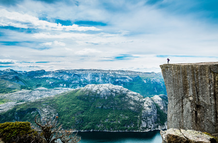 female photographer: Nature photographer tourist with camera shoots while standing on top of the mountain. Beautiful Nature Norway Preikestolen or Prekestolen.