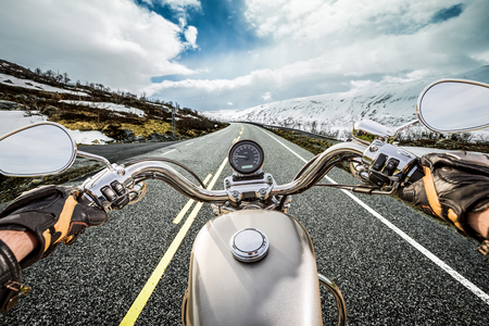 Biker rides a motorcycle on mountain serpentine. First-person view.