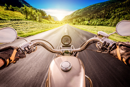 motor vehicle: Biker driving a motorcycle rides along the asphalt road. First-person view.