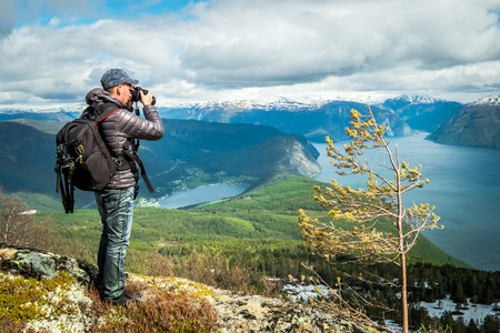 Fotógrafo de la naturaleza turística con cámara dispara mientras está de pie en la cima de la montaña. Hermosa Naturaleza Noruega. Foto de archivo