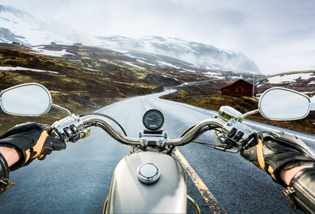 pass on: Biker rides a motorcycle on a slippery road through a mountain pass in Norway. Around the fog and snow. First-person view. Stock Photo