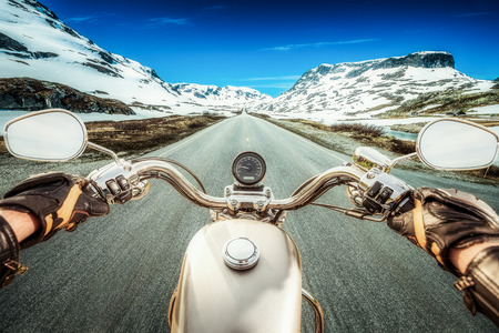 moto: Biker rides a motorcycle on a slippery road through a mountain pass in Norway. Around the fog and snow. First-person view. Stock Photo