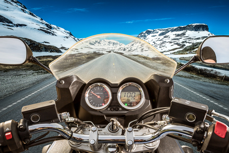 motorcycle road: Biker rides a motorcycle on a slippery road through a mountain pass in Norway. Around the fog and snow. First-person view. Stock Photo