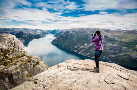 Fotógrafo de la naturaleza turística con cámara dispara mientras está de pie en la cima de la montaña. Hermosa Naturaleza Noruega Preikestolen o Prekestolen. Foto de archivo