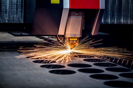 corte laser: CNC de corte por láser de metal, la tecnología industrial moderna. Pequeña profundidad de campo. Advertencia - tiroteo auténtico en condiciones difíciles. Un poco de grano poco y tal vez borrosa.