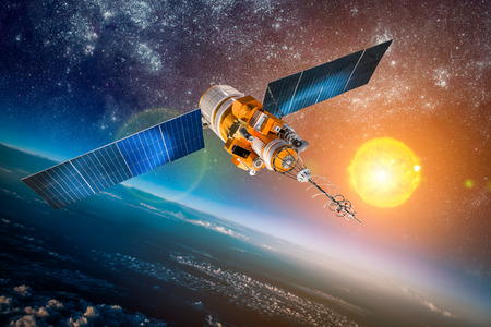 orbiting: Space satellite orbiting the earth on a background star sun Stock Photo