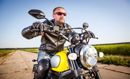 casco moto: Hombre motorista llevaba una chaqueta de cuero y gafas de sol sentado en su moto mirando el atardecer. Foto de archivo