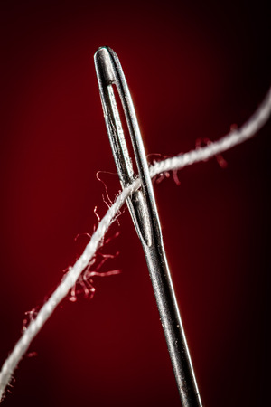 Needle with thread on a red background
