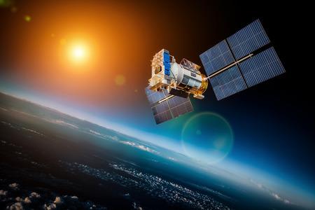 comunicación: Satélite espacial en órbita alrededor de la Tierra en una estrella de fondo y el sol Foto de archivo