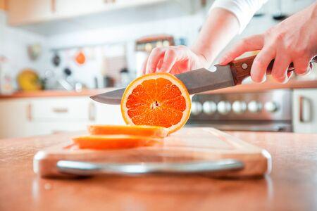 chef kitchen: Womans hands cutting fresh orange on kitchen Stock Photo