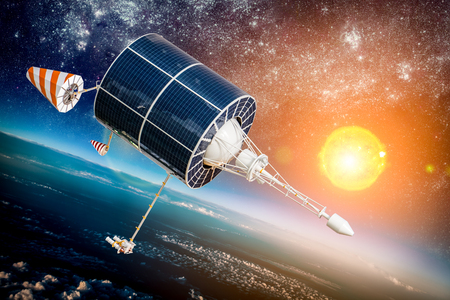 orbiting: Space satellite orbiting the earth on a background star and sun