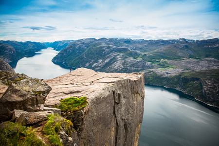 high view: Nature photographer tourist with camera shoots while standing on top of the mountain. Beautiful Nature Norway Preikestolen or Prekestolen.