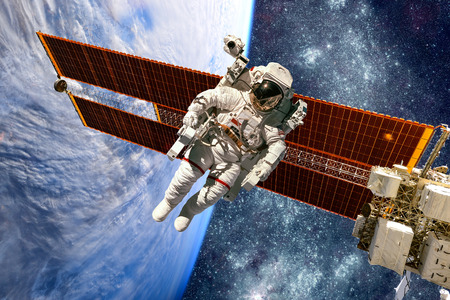 astronaut: International Space Station and astronaut in outer space over the planet Earth.