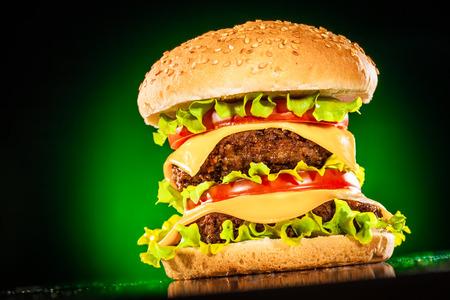HAMBURGUESA: Hamburguesa sabroso y apetecible, sobre un fondo verde oscuro