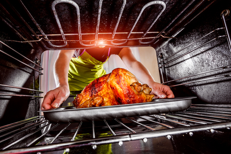 oven tray: Housewife prepares roast chicken in the oven, view from the inside of the oven. Cooking in the oven. Thanksgiving Day.