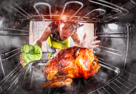 Funny Housewife overlooked roast chicken in the oven, so she had scorched (focus on chicken), view from the inside of the oven. Housewife perplexed and angry. Loser is destiny! Thanksgiving Day. Stock Photo