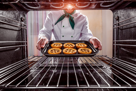 bakery oven: Chef prepares pastries in the oven, view from the inside of the oven. Cooking in the oven. Stock Photo