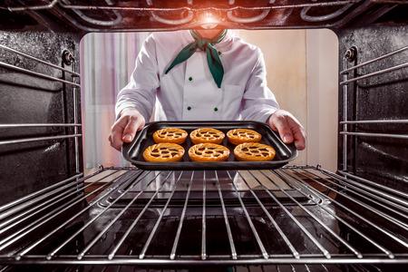 Küchenchef Backwaren in den Ofen, Blick aus dem Inneren des Ofens. Kochen in den Ofen. Standard-Bild - 45105392
