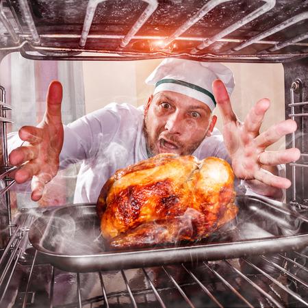 quemado: Cocinero divertido por alto el pollo asado en el horno, así que ella se había chamuscado, vista desde el interior del horno. Cocine perplejo y enojado. Loser es el destino! Foto de archivo