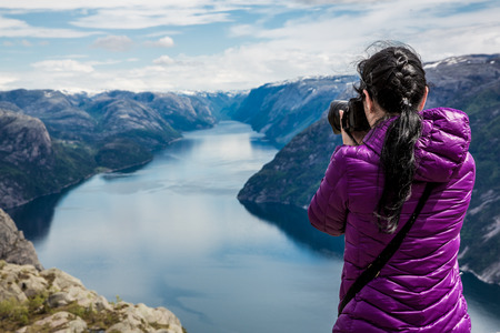 pro: Nature photographer tourist with camera shoots while standing on top of the mountain. Beautiful Nature Norway Preikestolen or Prekestolen.