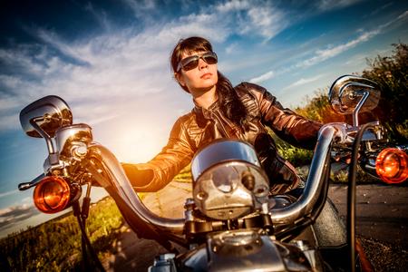 motorrad frau: Radfahrerm�dchen in einer Lederjacke auf einem Motorrad Blick auf den Sonnenuntergang. Filter in der Postproduktion angewendet. Lizenzfreie Bilder