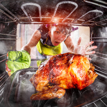 Funny Housewife overlooked roast chicken in the oven, so she had scorched (focus on chicken), view from the inside of the oven. Housewife perplexed and angry. Loser is destiny! Thanksgiving Day. Stockfoto