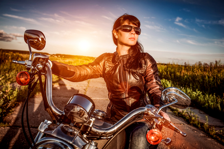 sexy female: Biker girl in a leather jacket on a motorcycle looking at the sunset. Filter applied in post-production.