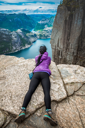 norway: Woman looking at the landscape from a height. Beautiful Nature Norway Preikestolen or Prekestolen. Stock Photo