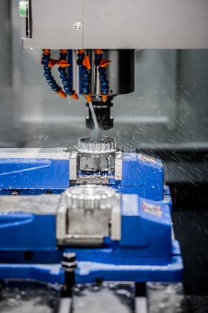 manufacturing equipment: Metalworking CNC milling machine. Cutting metal modern processing technology. Small depth of field. Warning - authentic shooting in challenging conditions. A little bit grain and maybe blurred.