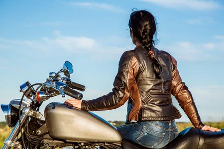 casco moto: Muchacha del motorista en una chaqueta de cuero en una motocicleta