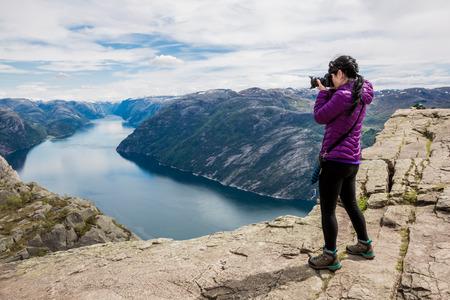 Natura turystyczny fotograf z aparatu fotograficznego strzela, stojąc na szczycie góry. Piękna przyroda Norwegia Preikestolen lub Prekestolen.