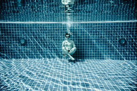 unusually: Man sitting on the bottom of the swimming pool under water