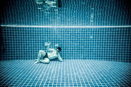 unusually: Man lies under water in a swimming pool Stock Photo