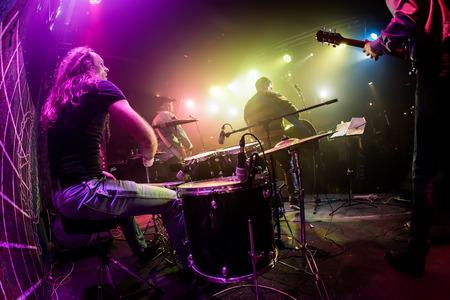 musico: El baterista de juego en el tambor establece en el escenario. Advertencia - Centrarse en el tambor, tiro auténtico con alta iso en condiciones de iluminación difíciles. Un pequeño grano de bits y efectos de movimiento borrosas.