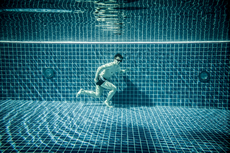 funny boy: Man under water runs along the bottom of a swimming pool