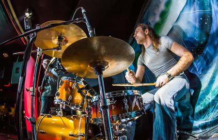 ステージにドラムセットを演奏するドラマー。警告 - ドラム、本格的な厳しい照明条件の高 iso での撮影に焦点を当てる。少し粒、モーションエフェ 写真素材