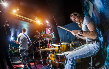background music: Drummer playing on drum set on stage. Warning - authentic shooting with high iso in challenging lighting conditions. A little bit grain and blurred motion effects.