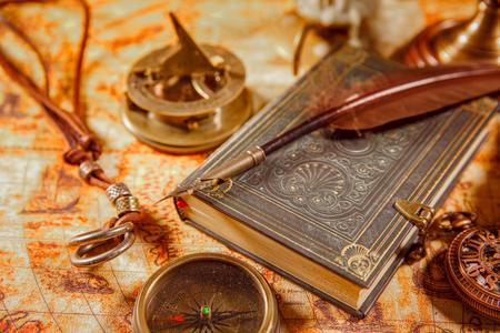 libros antiguos: Vintage bodegón - lupa, reloj de bolsillo, libro antiguo y pluma pluma de ganso tumbado en un viejo mapa en 1565.