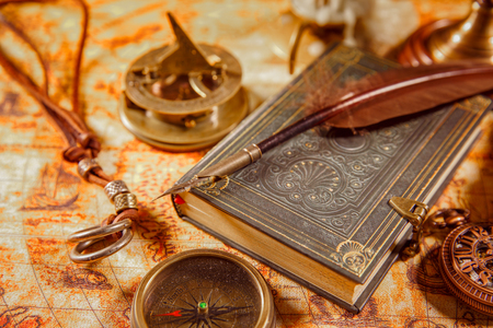 bygone: Vintage still life - magnifying glass, pocket watch, old book and goose quill pen lying on an old map in 1565.