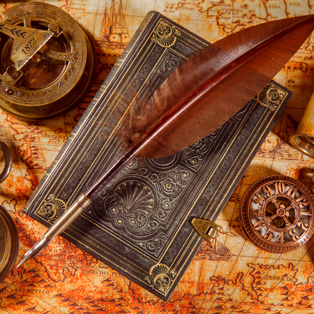 Vintage still life - magnifying glass, pocket watch, old book and goose quill pen lying on an old map in 1565.