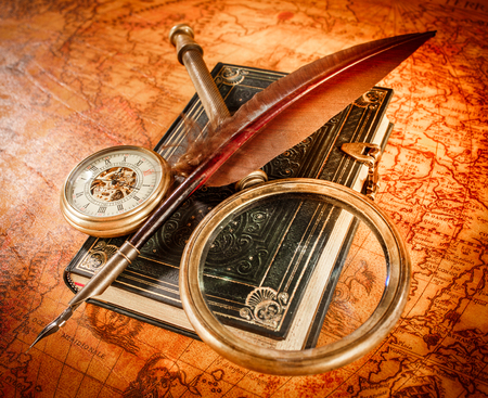 antique paper: Vintage still life - magnifying glass, pocket watch, old book and goose quill pen lying on an old map in 1565.