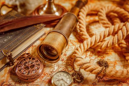 libros antiguos: Todavía de la vendimia vida - catalejo, reloj de bolsillo, libro antiguo y pluma pluma de ganso tumbado en un viejo mapa en 1565. Foto de archivo