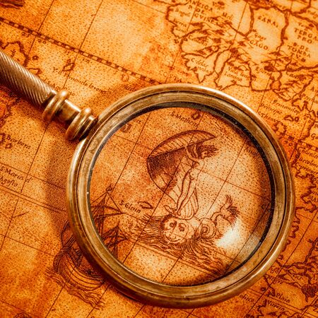 bygone: Vintage still life. Vintage magnifying glass lies on an ancient world map in 1565.