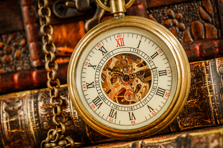 old time: Vintage Antique pocket watch on the background of old books