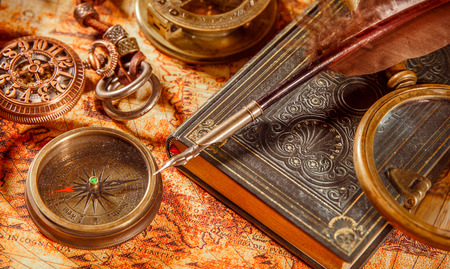 old books: Vintage still life - magnifying glass, pocket watch, old book and goose quill pen lying on an old map in 1565.